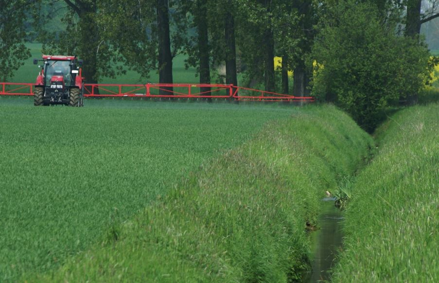 Photo showing a field with a tractor applying pesticides by spraying it onto the field surface. Next to the field is a small vegetation buffer strip which leads into a creek with water, and in the background are trees.